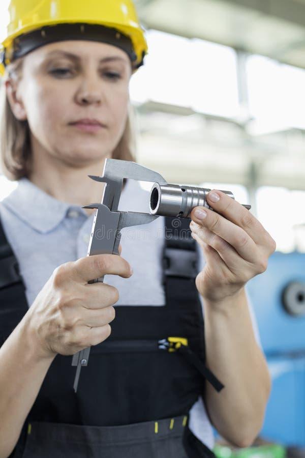 Madure el metal de medición del trabajador de sexo femenino con el calibrador en fábrica fotos de archivo