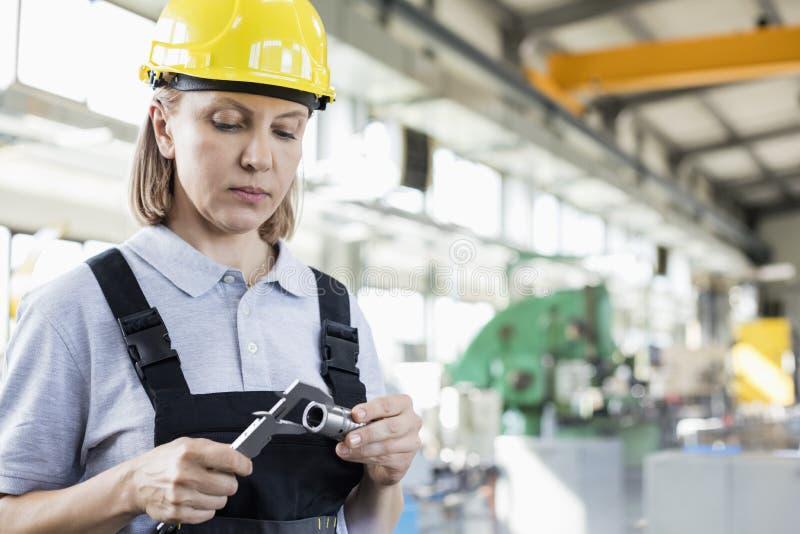 Madure el metal de medición del trabajador de sexo femenino con el calibrador en industria imagenes de archivo