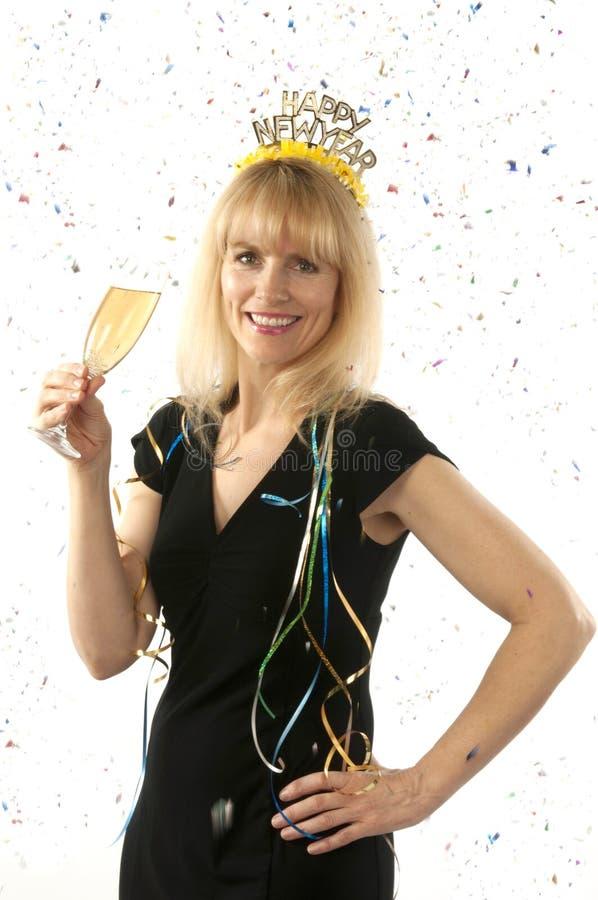 Madure a la mujer bastante rubia que celebra con un vidrio de champán en Noche Vieja imagen de archivo