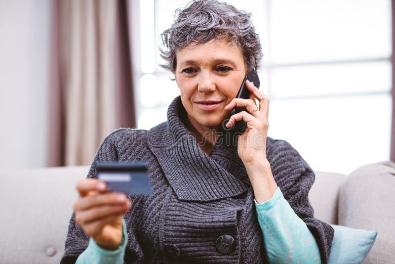 Madure a la mujer que sostiene la tarjeta de crédito mientras que habla en el teléfono móvil fotografía de archivo libre de regalías