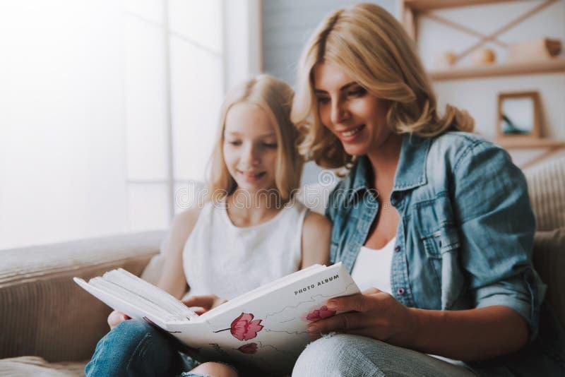 Madure a la mujer rubia con el álbum de foto de observación de la hija linda en el sofá fotografía de archivo