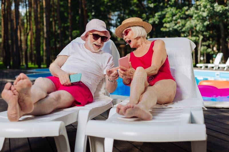 Madure a la mujer rubio-cabelluda que muestra a fotos divertidas su marido imagen de archivo