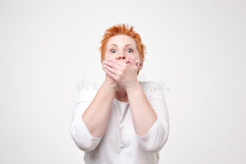 Madure a la mujer sorprendente que cubre su boca con la mano en fondo gris No diré este secreto cualquiera fotografía de archivo libre de regalías