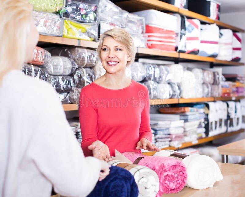 Madure las sobrecamas de ofrecimiento del vendedor de sexo femenino a la mujer joven en t casero foto de archivo libre de regalías