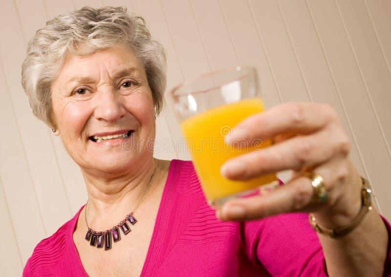 Madure a una más vieja señora con el vidrio de zumo de naranja imagen de archivo libre de regalías