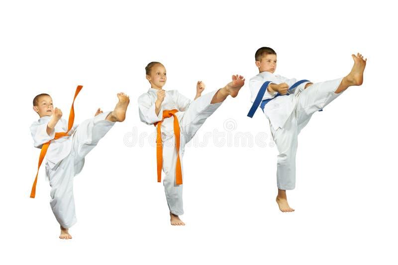 Mae-geri反撞力打三karategi的运动员 免版税库存图片