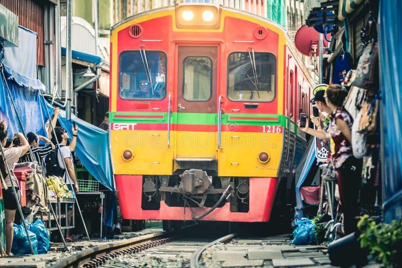 Mae Klong järnvägsmarknad Tåg som passerar några centimeter från människor och bås arkivfoton