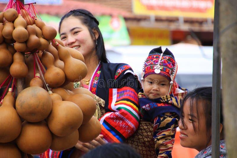 MAE SALONG, ТАИЛАНД - 17-ОЕ ДЕКАБРЯ 2017: Женщина от племени холма Akha в северном Таиланде нося ее младенца на задней части на р стоковые фотографии rf