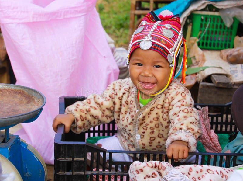 MAE SALONG, TAILANDIA - 17 DE DICIEMBRE 2017: Retrato de un bebé feliz del niño de la tribu de la colina de Akha en una caja que  fotos de archivo libres de regalías