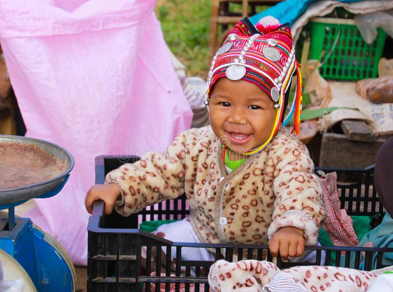 MAE SALONG, THAILAND - DECEMBER 17. 2017: Portrait of a happy toddler baby from Akha hill tribe in a shopping box on market with royalty free stock photos