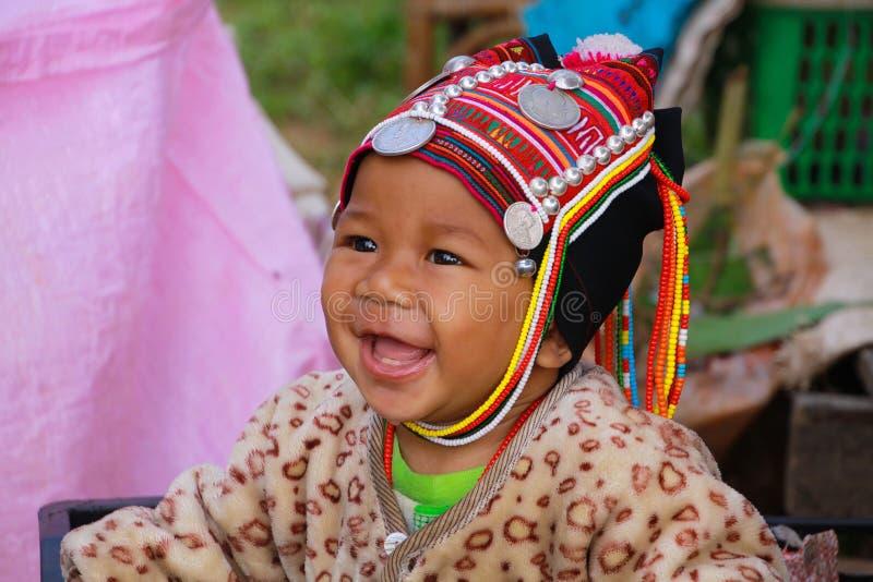 MAE SALONG, THAILAND - DECEMBER 17 2017: Portret van een gelukkige peuterbaby van Akha-heuvelstam in een het winkelen doos op mar royalty-vrije stock afbeelding