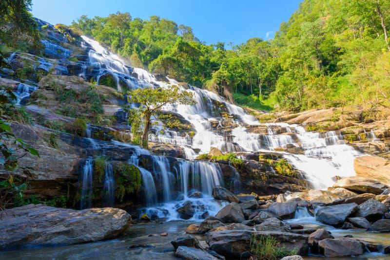 Mae Ya vattenfall med gröna träd och backgroundatDoi Inthanon för blå himmel nationalpark, en av de berömda vattenfallen royaltyfria bilder