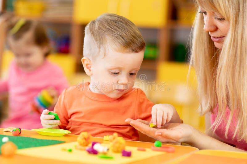 Maestra con bebés en creche Niños en clases en kindergarten fotos de archivo