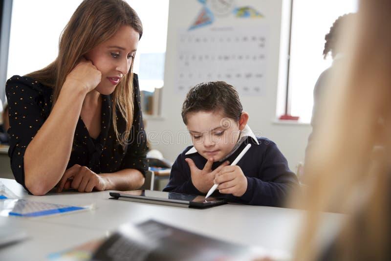 Maestra joven que trabaja con un colegial de Síndrome de Down que se sienta en el escritorio en una sala de clase de la escuela p imágenes de archivo libres de regalías