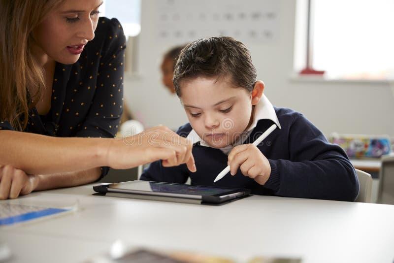 Maestra joven que trabaja con un colegial de Síndrome de Down que se sienta en el escritorio usando una tableta en una sala de cl foto de archivo