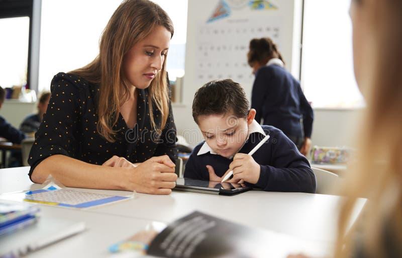 Maestra joven que trabaja con un colegial de Síndrome de Down que se sienta en el escritorio usando una tableta y una aguja en un imágenes de archivo libres de regalías