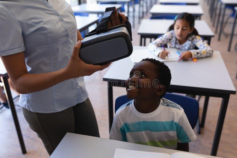 Maestra que lleva las auriculares de la realidad virtual al colegial en el escritorio en sala de clase foto de archivo libre de regalías