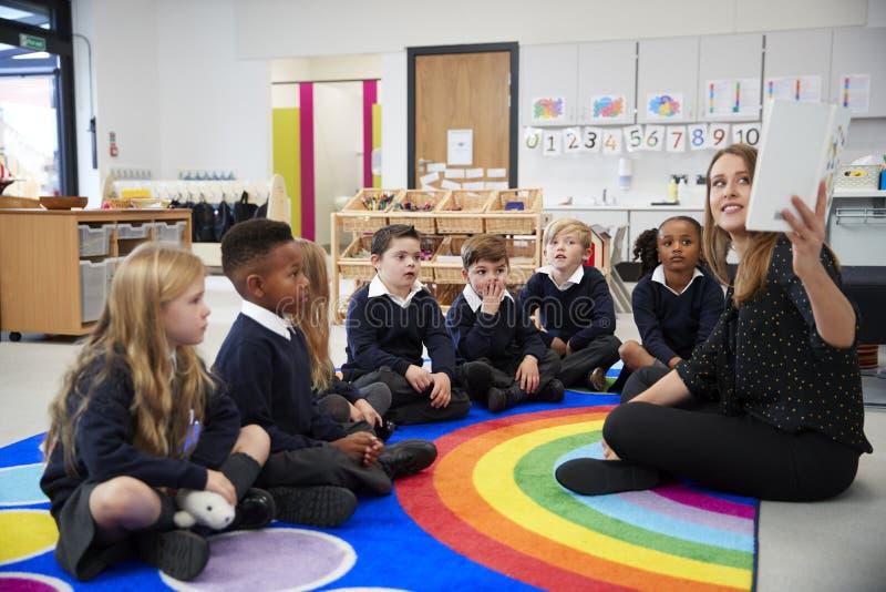 Maestra que soporta un libro delante de su clase de niños de la escuela primaria que se sientan en el piso en una sala de clase,  fotos de archivo