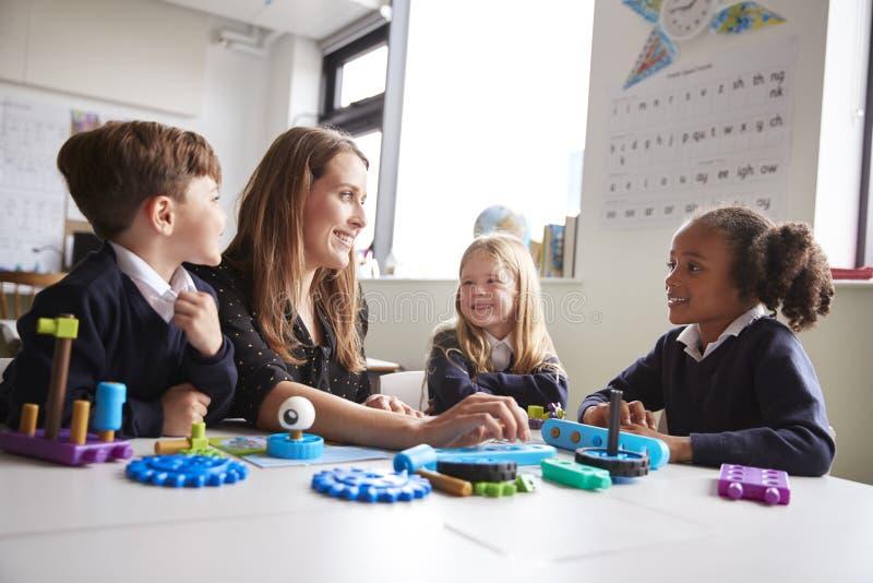 Maestra y tres niños de la escuela primaria que se sientan en una tabla en una sala de clase que trabaja con los juguetes educati imagen de archivo