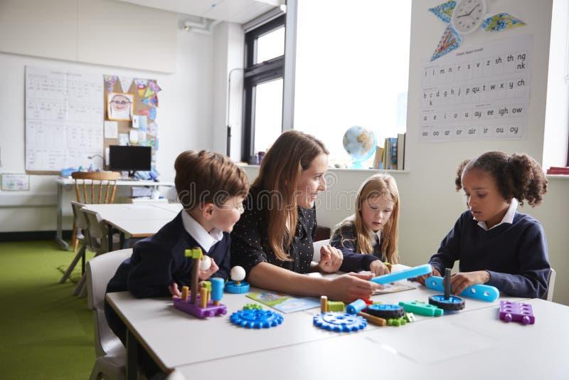 Maestra y tres niños de la escuela primaria que se sientan en una tabla en una sala de clase que trabaja con los juguetes educati fotos de archivo libres de regalías