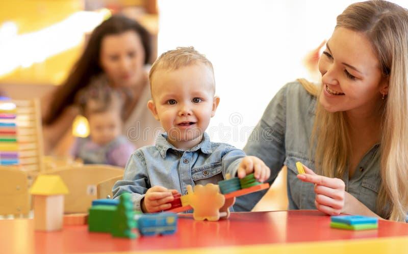Maestro de jardín de infancia que juega con el niño en cuarto de niños Juguetes de desarrollo para el preescolar imagen de archivo