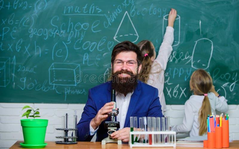 Maestro di scuola di biologia Lavoro barbuto dell'insegnante dell'uomo con il microscopio e le provette nell'aula di biologia Gio fotografie stock