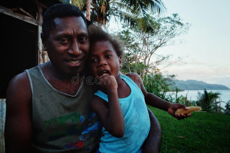 maestro di scuola Mr del villaggio Gibson con sua figlia sveglia davanti alla loro casa su una collina sopra la riva dell'oceano fotografia stock