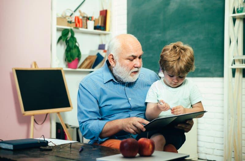 Maestros y alumnos que aprenden juntos en la escuela Proceso educativo Abuelo y nieto aprendiendo juntos foto de archivo