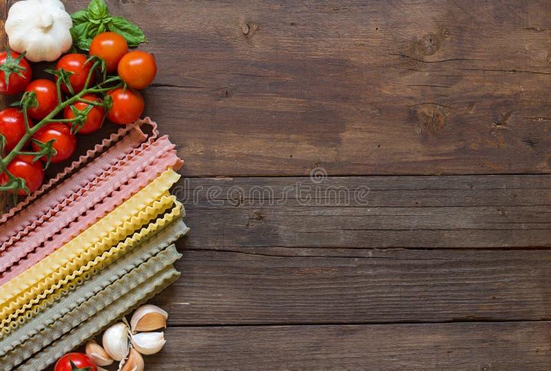 Mafalde面团、橄榄油、大蒜和蕃茄在木tabl 图库摄影