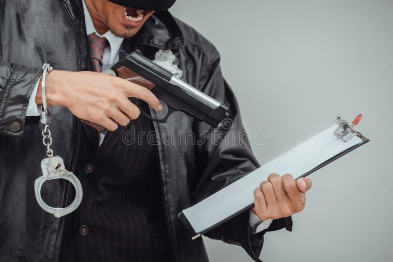 Maffiaman i dräkten som räknar vapnet på vit bakgrund Den ilskna affärsmannen förstörde tillhörigheter royaltyfria bilder