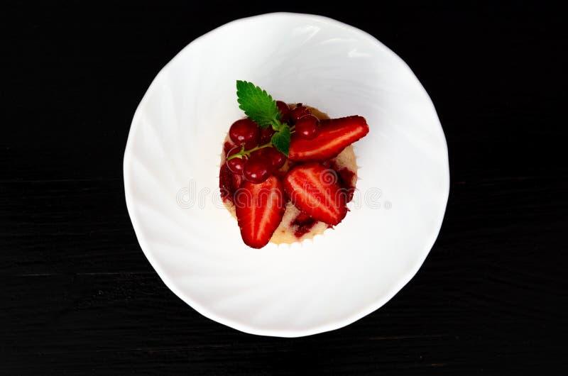 Maffin com morango e hortelã no fundo preto fotografia de stock