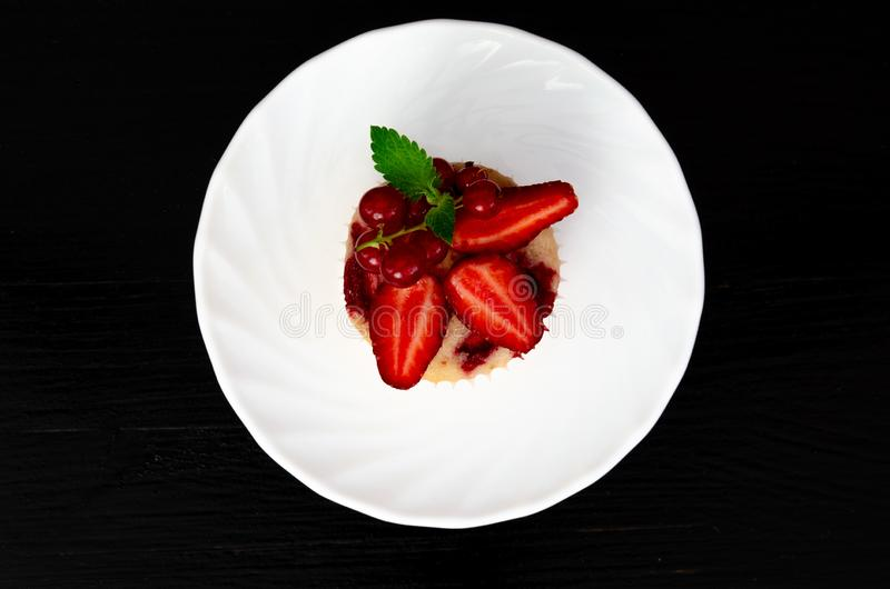 Maffin with strawberry and mint on black background stock photography
