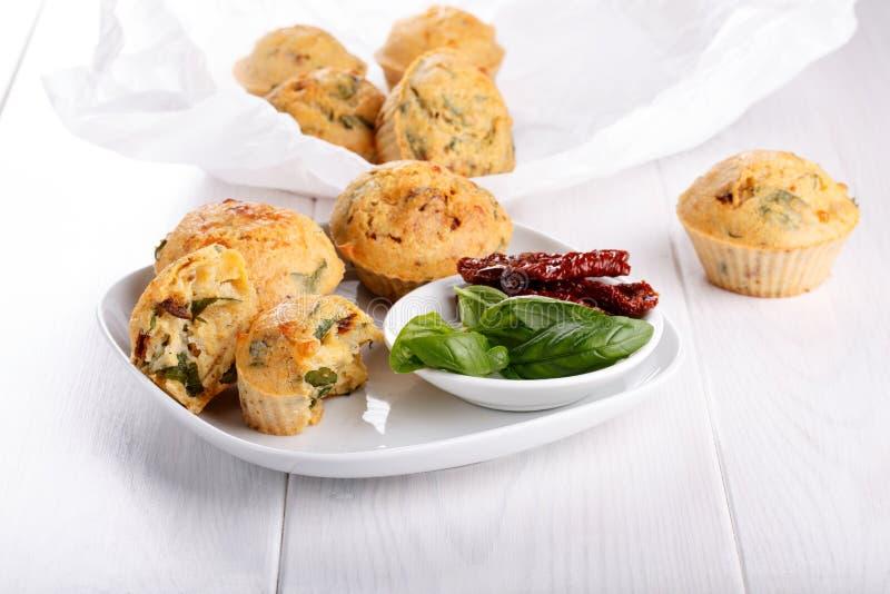 Maffins saborosos do queijo com manjericão e o tomate sol-secado fotografia de stock
