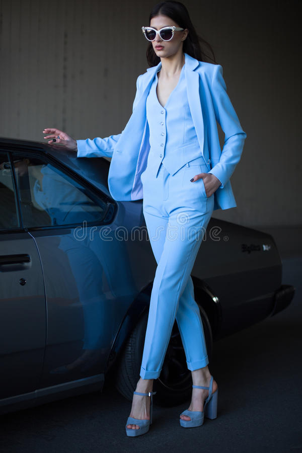 Mafia lady outside japonese car in the sea port. Fashion girl standing next to a retro sport car on the sun. stock photos