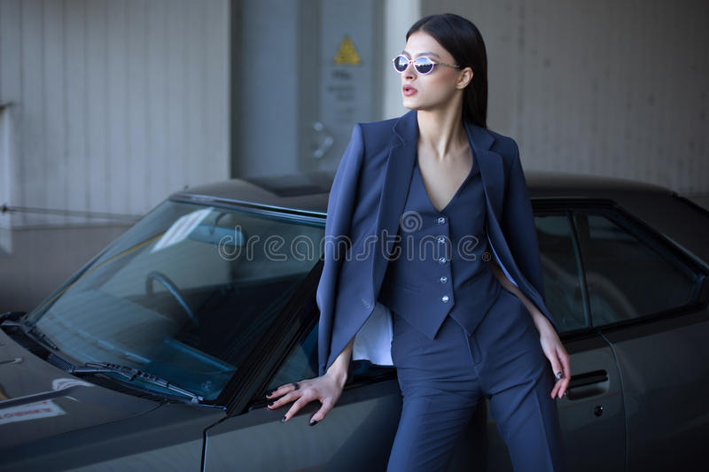 Mafia lady outside japonese car in the sea port. Fashion girl standing next to a retro sport car on the sun royalty free stock images