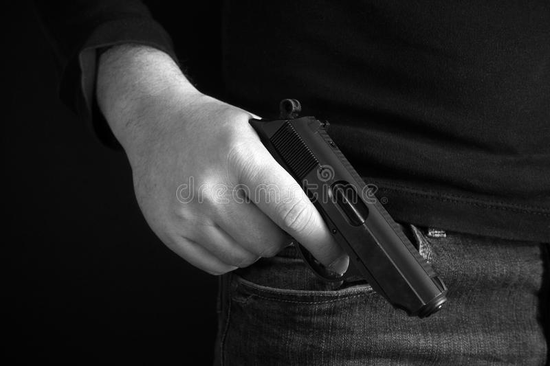 Mafioso holds pulled out gun, isolated on dark background back and white photo. stock images