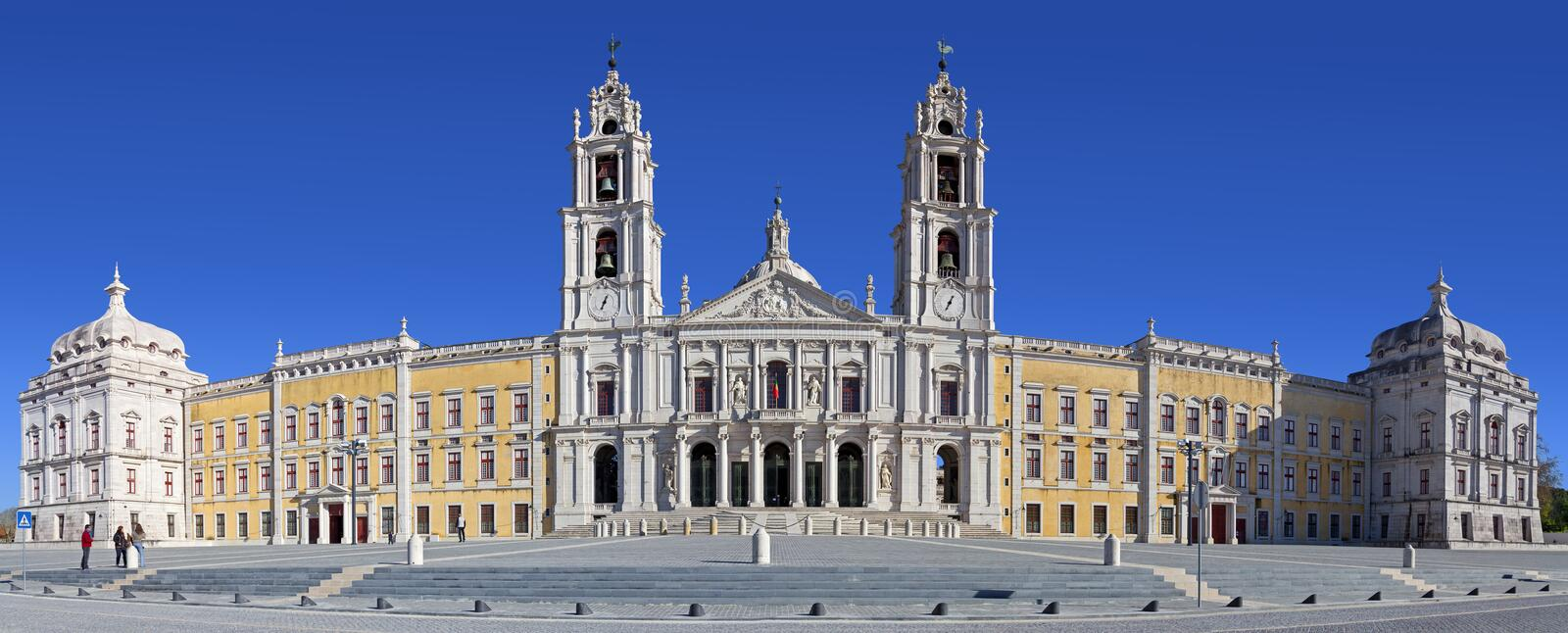 Mafra National Palace, Convent and Basilica. Mafra, Portugal - September 02, 2013: Tourists stroll in front of the Mafra National Palace, Convent and Basilica stock photos