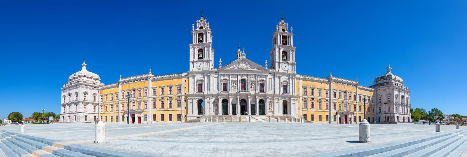 Mafra National Palace, Convent and Basilica in Portugal. Mafra, Portugal - September 02, 2014: Tourists stroll in front of the Mafra National Palace, Convent and stock photography