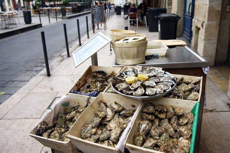 Magasin av öppnade nya ostron på is med citronen och askar av oöppnade ostron på ett gatakafé i Bordeaux, Aquitaine region fran arkivfoto