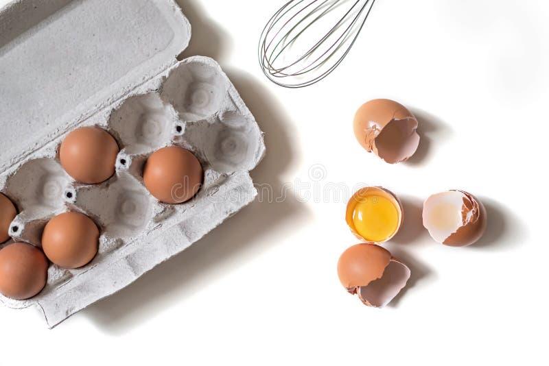 Magasin av nya rå ägg och det brutna äggskalet på vit isolerad bakgrund royaltyfri bild