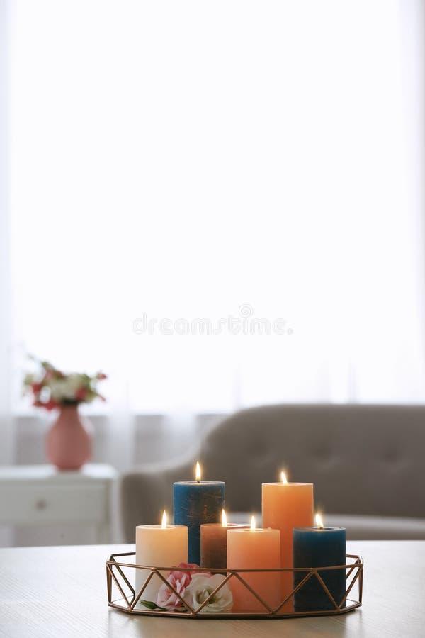 Magasin med bränningstearinljus och blommor på tabellen i vardagsrum arkivbild