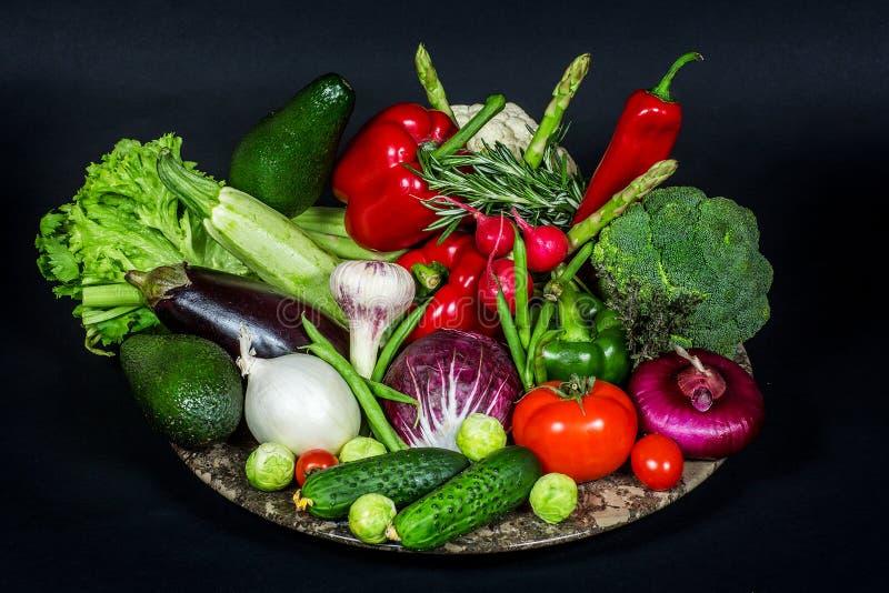 Magasin med högen av nya grönsaker på den svarta bakgrunden royaltyfri foto