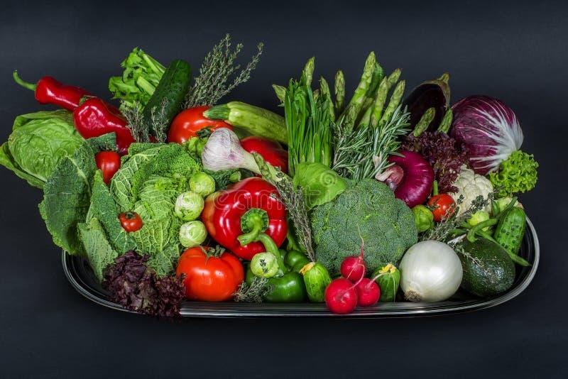 Magasin med högen av nya grönsaker på den svarta bakgrunden arkivbilder