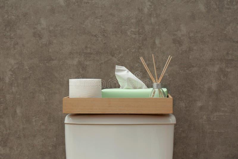 Magasin med rulle av papper, servetter och vassluftfresheneren på toalettbehållare nära den gråa väggen arkivfoton
