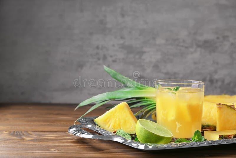 Magasin med skivat ananas och exponeringsglas av ny fruktsaft på trätabellen arkivbild