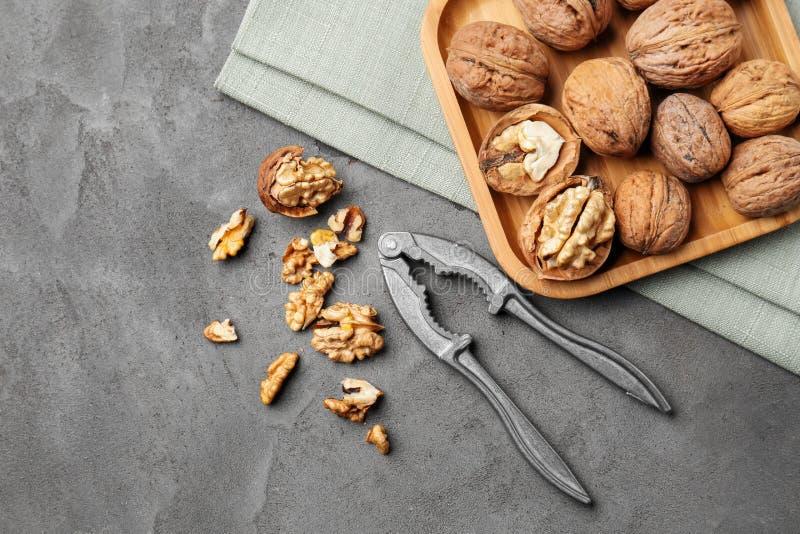 Magasin med smakliga valnötter och nötknäpparen på den gråa tabellen fotografering för bildbyråer