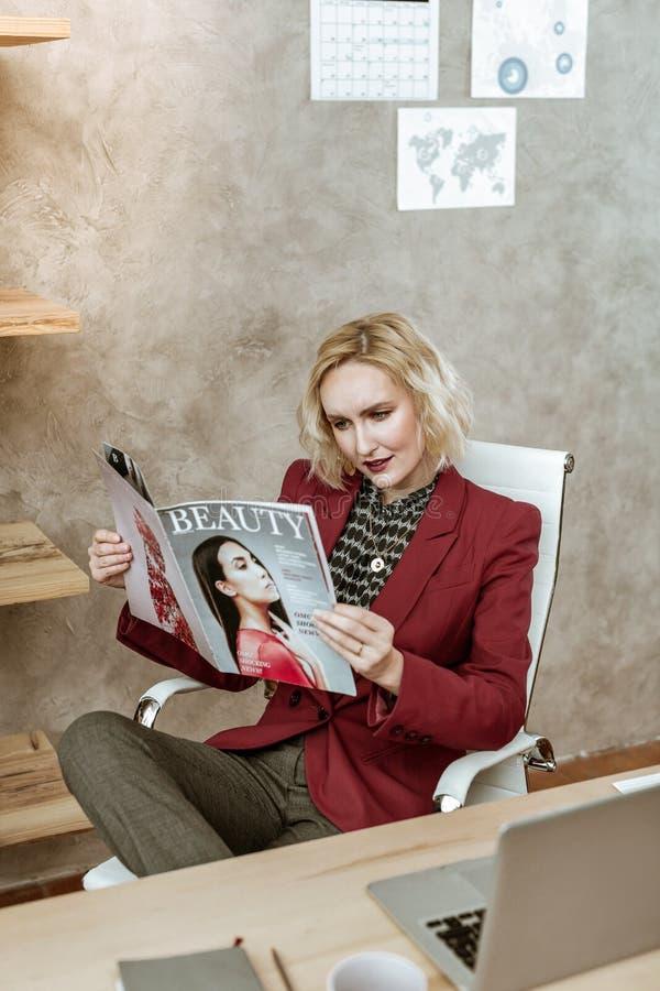 Magazine curieux de beauté de lecture de femme belle au travail images stock