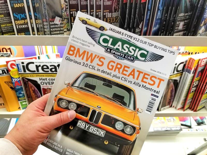 Magazine de classique et de voiture de sport dans une main images libres de droits