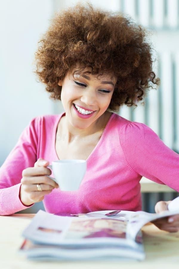 Magazine de lecture de femme en café photographie stock