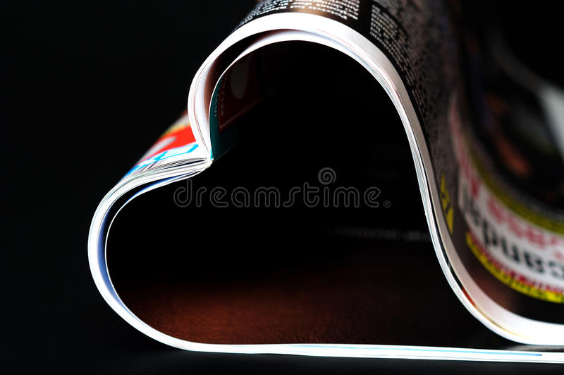 Magazine. In heart shape on black royalty free stock photos